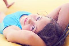 逗人喜爱的女孩放松的说谎在可膨胀的床垫特写镜头画象 图库摄影