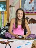 逗人喜爱的女孩放置在她的床的-打电子游戏 库存照片