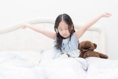 逗人喜爱的女孩早晨醒在卧室 库存照片