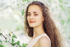逗人喜爱的女孩春天画象有长的卷发的在开花 免版税库存照片
