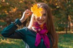年轻逗人喜爱的女孩是微笑和拿着板料在眼睛特写镜头附近 免版税图库摄影