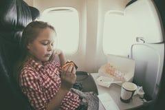 逗人喜爱的女孩有膳食在飞机,当飞行时 库存图片