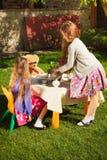 逗人喜爱的女孩有茶会在围场 免版税库存照片