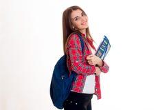 年轻逗人喜爱的女孩格子花呢上衣的和有在后面微笑和拿着文件夹的一个公文包的 库存照片