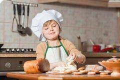 逗人喜爱的女孩烘烤曲奇饼 库存图片