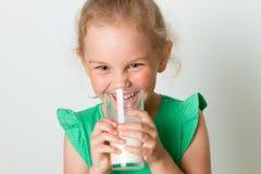 逗人喜爱的女孩玻璃藏品牛奶 库存图片