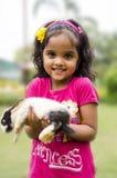 逗人喜爱的女孩用兔子。 免版税库存照片