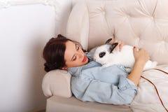 逗人喜爱的女孩用在她的胳膊的一只兔子 免版税库存照片
