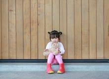 逗人喜爱的女孩画象坐和拥抱玩具熊对木板条墙壁 免版税图库摄影