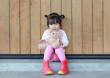 逗人喜爱的女孩画象坐和拥抱玩具熊对木板条墙壁 库存图片