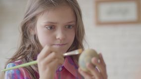 逗人喜爱的女孩画象用长发绘画使用坐直在厨房关闭的刷子的复活节彩蛋 E 股票视频