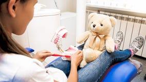 逗人喜爱的女孩的特写镜头图象有玩具熊等待的牙医的诊所的 图库摄影