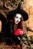 逗人喜爱的女孩穿戴了到万圣夜服装在黑暗的森林里 免版税图库摄影