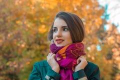 逗人喜爱的女孩立场在公园看起来去并且保留手围巾 免版税库存图片