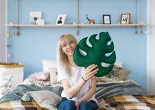 逗人喜爱的女孩纵向 她在手中拿着一个绿色枕头类似于叶子 图库摄影