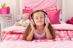 逗人喜爱的女孩耳机听的音乐 免版税库存图片