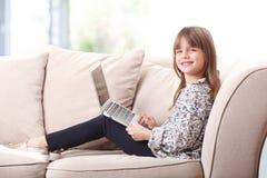 逗人喜爱的女孩膝上型计算机 库存照片
