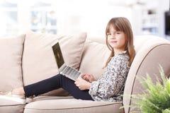 逗人喜爱的女孩膝上型计算机 免版税库存图片