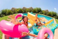 逗人喜爱的女孩获得与朋友的乐趣在游泳场 库存照片