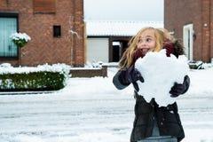 逗人喜爱的女孩获得乐趣在雪 免版税图库摄影