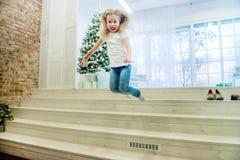 逗人喜爱的女孩跳跃从楼梯的便服的 库存照片