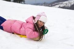 逗人喜爱的女孩雪撬雪 库存图片
