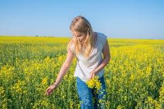 逗人喜爱的女孩,金发碧眼的女人收集在领域的黄色花在蓝色下 免版税库存照片