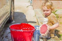 逗人喜爱的女孩洗涤的汽车 库存照片