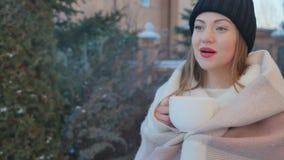 逗人喜爱的女孩画象有红色嘴唇的在冬天喝热的茶温暖户外 股票录像
