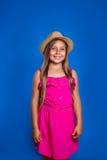 年轻逗人喜爱的女孩画象桃红色礼服和帽子的在蓝色背景 暑假和旅行概念 免版税图库摄影