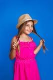 年轻逗人喜爱的女孩画象桃红色礼服和帽子的在蓝色背景 暑假和旅行概念 库存图片