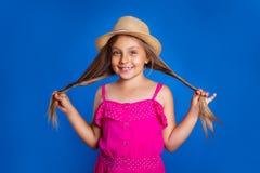 年轻逗人喜爱的女孩画象桃红色礼服和帽子的在蓝色背景 暑假和旅行概念 图库摄影