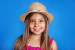 年轻逗人喜爱的女孩画象桃红色礼服和帽子的在蓝色背景 暑假和旅行概念 免版税库存图片