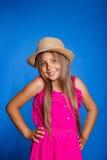 年轻逗人喜爱的女孩画象桃红色礼服和帽子的在蓝色背景 暑假和旅行概念 免版税库存照片