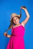 年轻逗人喜爱的女孩画象桃红色获得礼服和的帽子的在蓝色背景的乐趣 暑假和旅行概念 免版税库存图片
