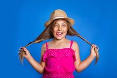 年轻逗人喜爱的女孩画象桃红色获得礼服和的帽子的在蓝色背景的乐趣 暑假和旅行概念 免版税库存照片