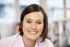 逗人喜爱的女实业家画象在办公室,看照相机 免版税库存图片