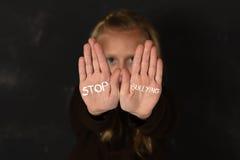 逗人喜爱的女小学生惊吓了哀伤请求显示有中止胁迫的文本的帮忙手写在她的棕榈 免版税库存图片