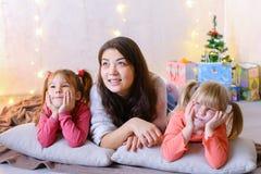 逗人喜爱的女性和两个小女孩孩子,摆在为照相机和 库存照片