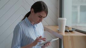 逗人喜爱的女性开会在自助食堂和使用数字式片剂 影视素材