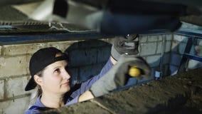 逗人喜爱的女性技工在飞机棚修理一辆汽车 股票录像