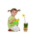 逗人喜爱的女花童浇灌的一点 库存图片