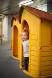逗人喜爱的女婴在塑料房子里 免版税库存图片