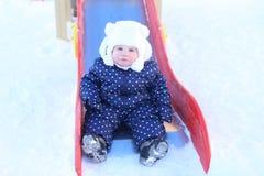 逗人喜爱的女婴在温暖的衣裳的11个月室外在冬天 图库摄影