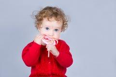逗人喜爱的女婴用一个心形的糖果 免版税库存图片