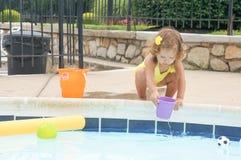 逗人喜爱的女婴获得乐趣在水池 免版税库存照片