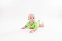 逗人喜爱的好奇婴孩在她的胃和看说谎照相机 库存图片