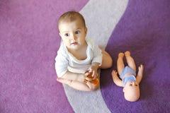 逗人喜爱的好矮小的女婴坐有玩偶的紫色地毯 免版税库存照片
