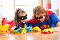 逗人喜爱的妇女和她的孩子女儿穿戴了象清洗地板和微笑的超级英雄 库存照片