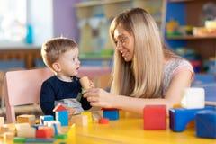 逗人喜爱的妇女和演奏教育玩具的男婴在托婴所或托儿所 免版税库存图片